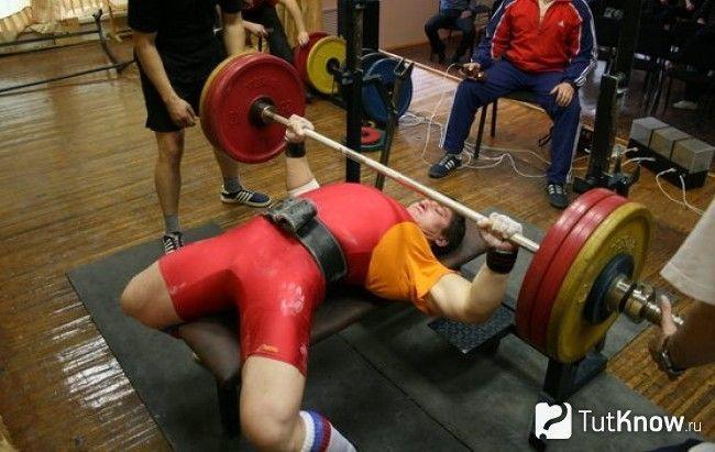 Спортсмен виконує жим в положенні лежачи