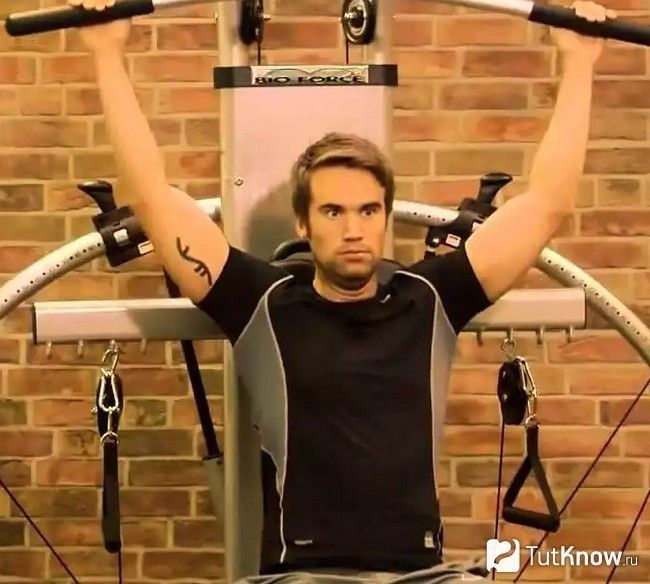 Чоловік виконує вправу на тренажері