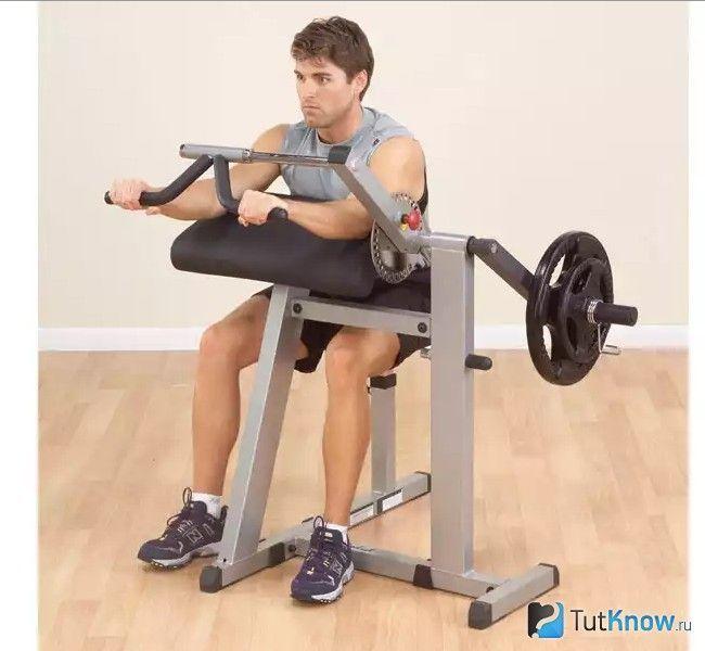 Спортсмен сидячи виконує вправу на тренажері