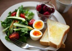 Грінки, варені яйця, овочі і вишня на тарілці