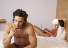 Чоловік сидить на ліжку
