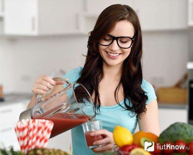 Дівчина наливає сік в склянку
