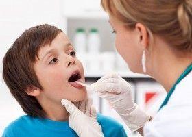 Медсестра дивиться горло хлопчикові