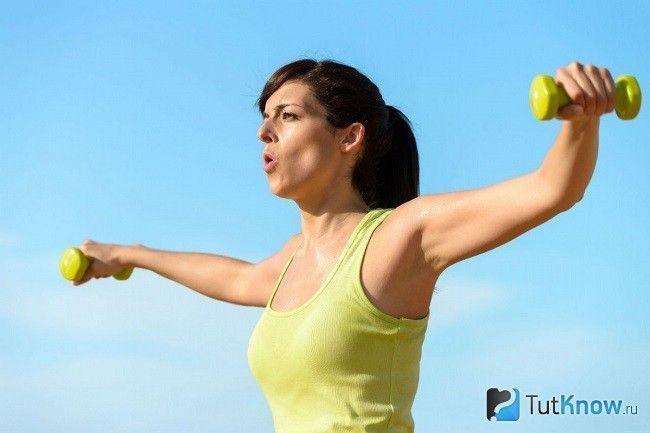 Дівчина виконує дихальну гімнастику з гантелями