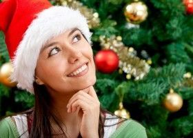 Дівчина в шапці Діда Мороза на фоні ялинки