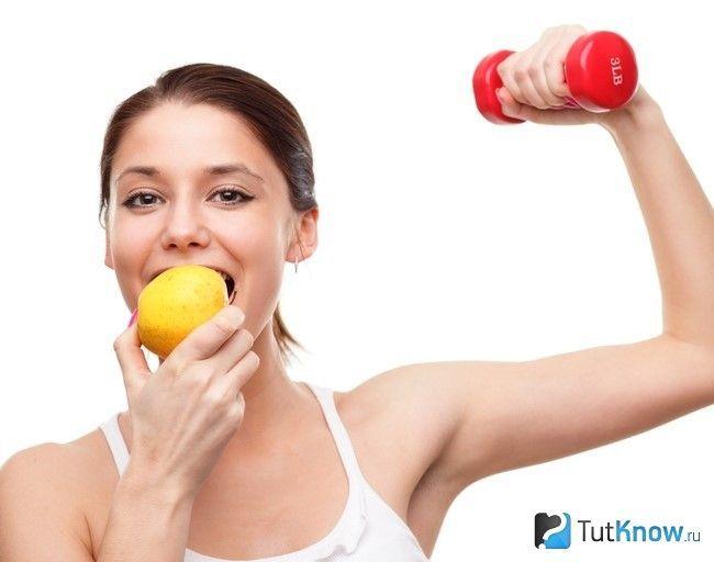 Дівчина їсть яблуко і тримає гантель