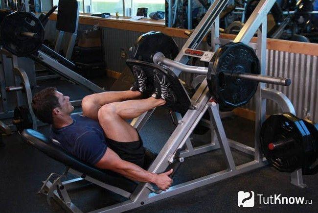 Спортсмен виконує жим ногами на тренажері