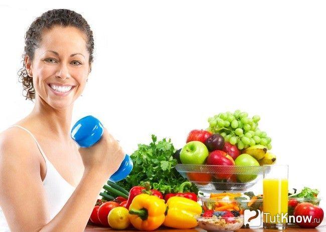 Дівчина з гантелей біля овочів і фруктів