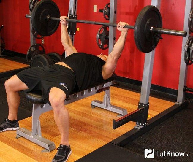 Спортсмен виконує жим лежачи широким хватом