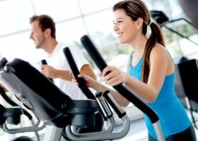 Чоловік і жінка тренуються на кардиотренажерах