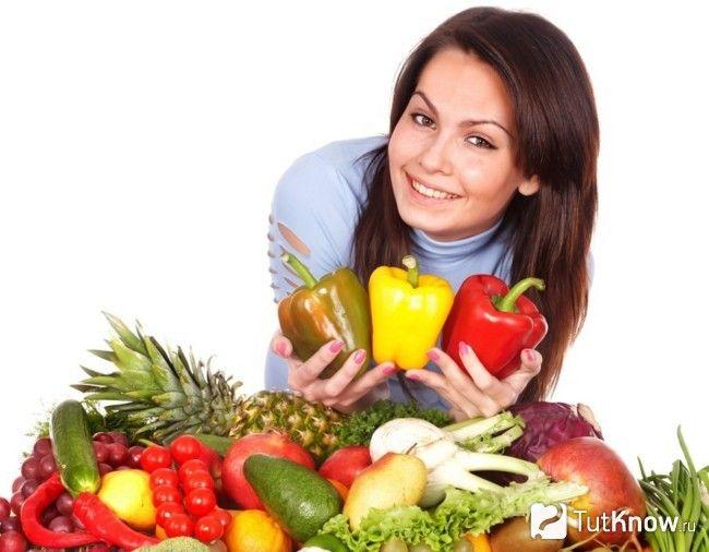 Дівчина біля овочів і фруктів