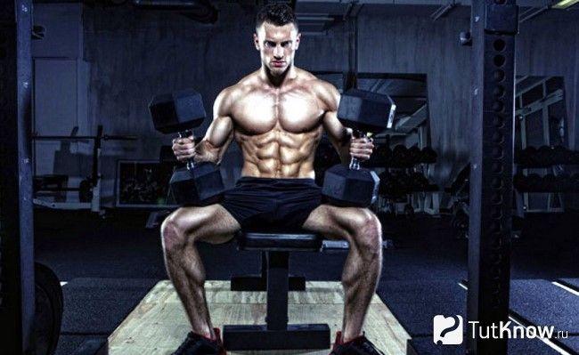 Спортсмен сидить на лаві з гантелями в руках