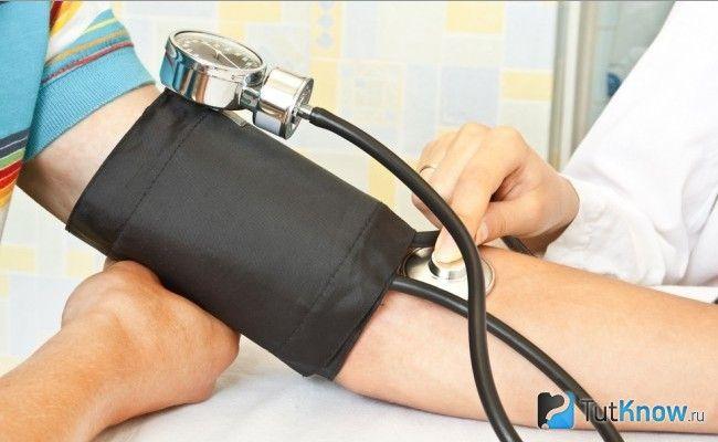Лікар вимірює тонометром артеріальний тиск